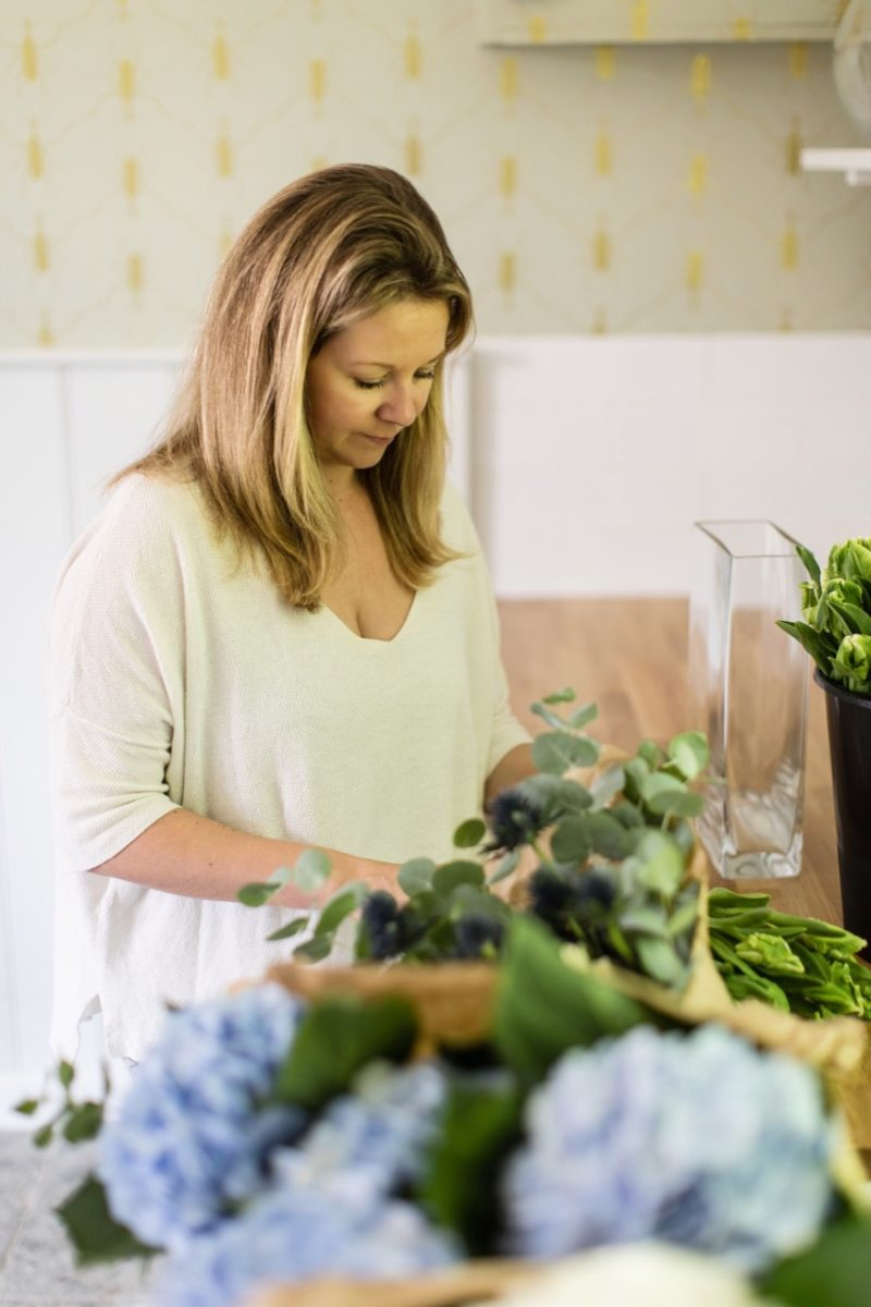 Laura Butler-Madden arranging flowers at home.
